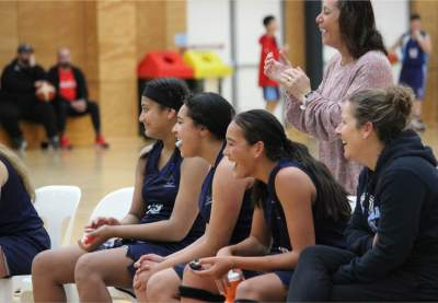 Teenage girls cheer from sideline at basketball game